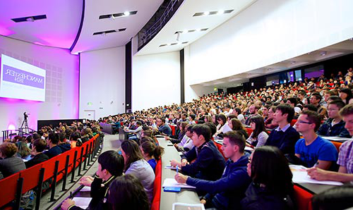 Students attending an even in a full lecture theatre