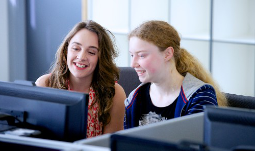 Pair of female students at computer watching webinar