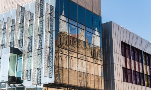Old buildings of 英国云顶集团 reflected in the windows of the modern Alan Gilbert Learning Commons building